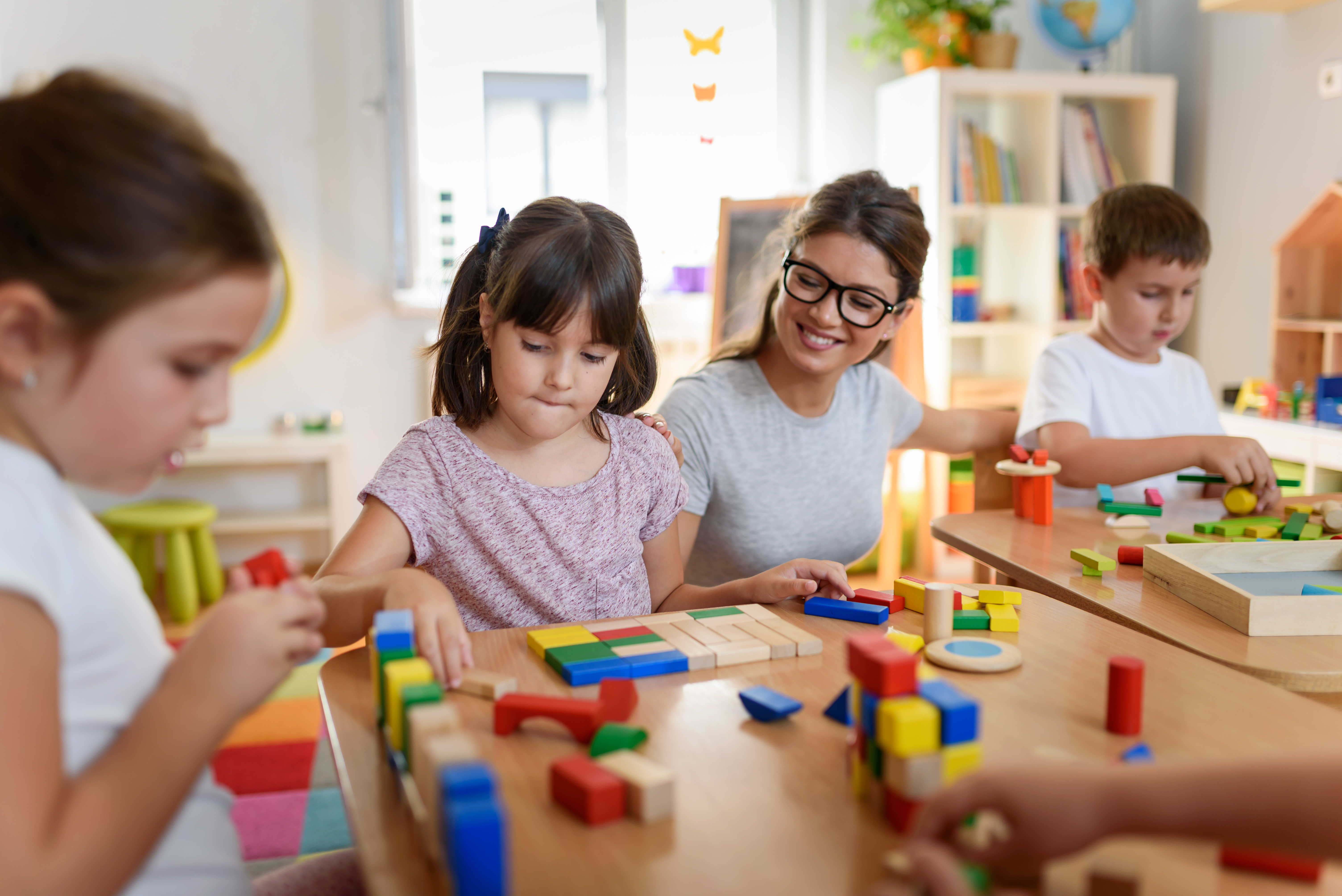 child care worker playing with toys with students
